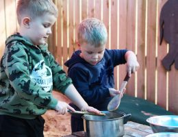 Friends playing in mud kitchen