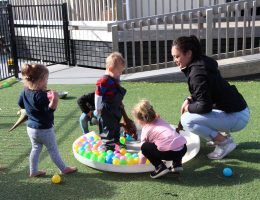 teacher with group of toddlers enjoying outdoor environment
